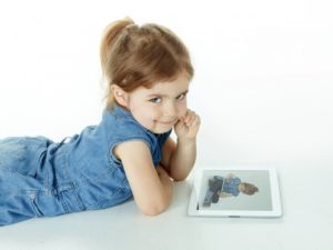 Little girl is watching concentrated photographs on touchpad © Karin & Uwe Annas - Fotolia