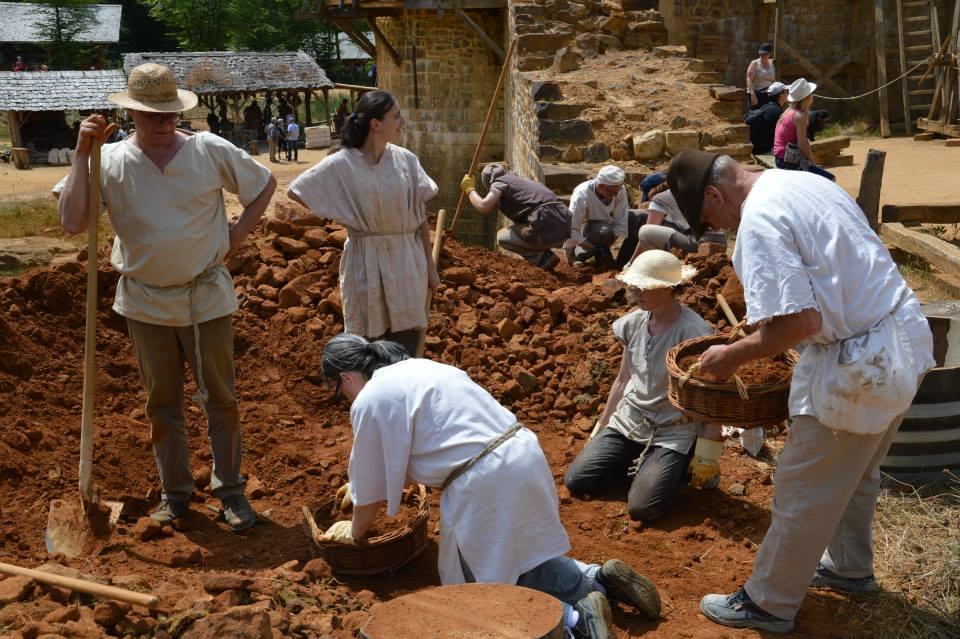 Chantier médiéval de Guédelon : les œuvriers ramassent de la terre pour la fabrication du mortier / Photo Fabien Soyez