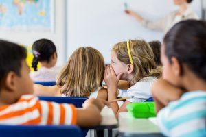 Schoolgirls gossiping in classroom © WavebreakmediaMicro