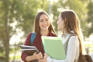 Two happy students walking and talking each other in a campus at sunset with a warm light / Antonio Guillem / Shutterstock