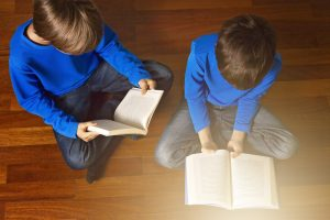 Children reading books on the floor at home. / Shutterstock