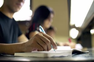 Students doing homework and preparing exam at university, closeup of young man writing in college library / Shutterstock