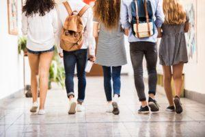 Unrecognizable teenage students in high school hall / Shutterstock