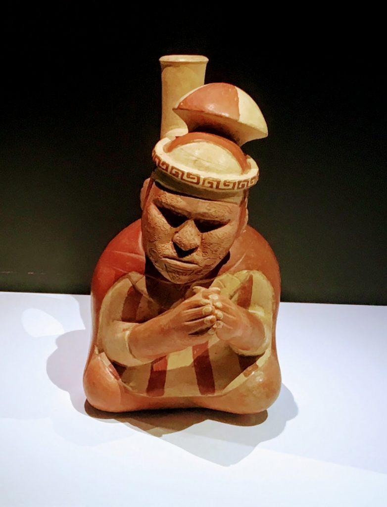 """Bouteille à anse-goulot en étrier, représentant un prêtre / chamane aveugle en prière, au visage scarifié ; Moche III, 300-400 ap JC, céramique / musée du Quai Branly, exposition """"Le Pérou avant les Incas"""""""